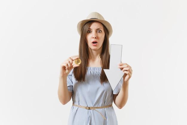 젊은 충격을 받은 슬픈 여성은 비트코인, 황금색 동전, 흰색 배경에 격리된 가치 하락 화살표를 들고 있습니다. 금융 및 비즈니스, 온라인 가상 통화 개념입니다. 광고 영역입니다. 공간을 복사합니다.