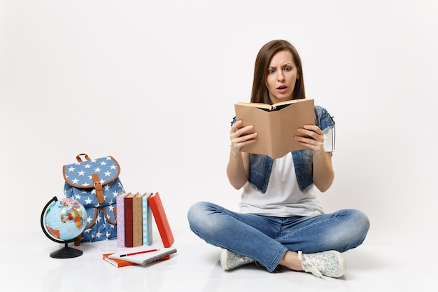 Young shocked scared woman student in denim clothes holding book reading sitting near globe, backpack, school books