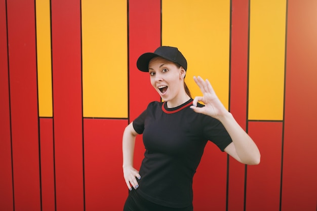 Молодая шокированная улыбающаяся спортивная красивая брюнетка женщина в черной униформе и кепке стоит и показывает знак ок до или после тренировки на открытом воздухе на ярком фоне