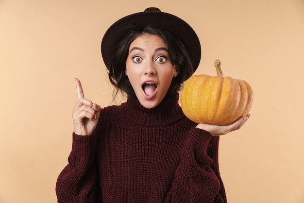 Young shocked surprised brunette woman isolated over beige wall wall holding pumpkin pointing have an idea.