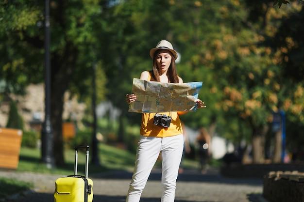 여행 가방 도시 지도가 있는 노란색 여름 캐주얼 옷 모자를 쓴 젊은 여행자 관광 여성은 야외 도시를 걷고 있습니다. 주말 휴가를 여행하기 위해 해외로 여행하는 소녀. 관광 여행 라이프 스타일.