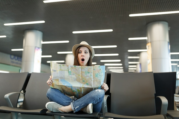 足を組んでショックを受けた若い旅行者の観光客の女性は、国際空港のロビーホールで待っているルートを探して、紙の地図を保持します