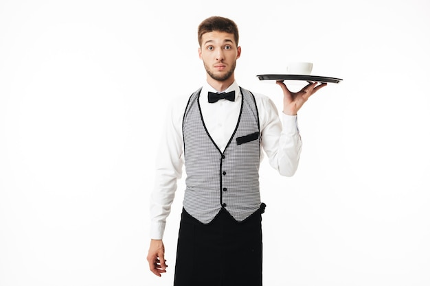 Young shocked waiter in uniform holding tray with cup of coffee while amazedly