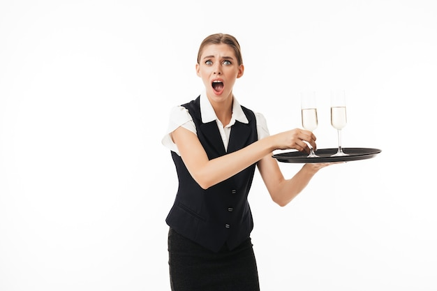Young shocked waitress in uniform amazedly