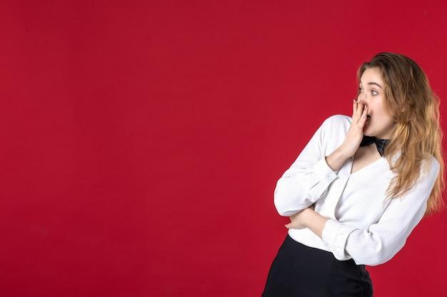 若いショックを受けたウェイトレスの女性の首に蝶と赤い背景の右側に何かを指しています