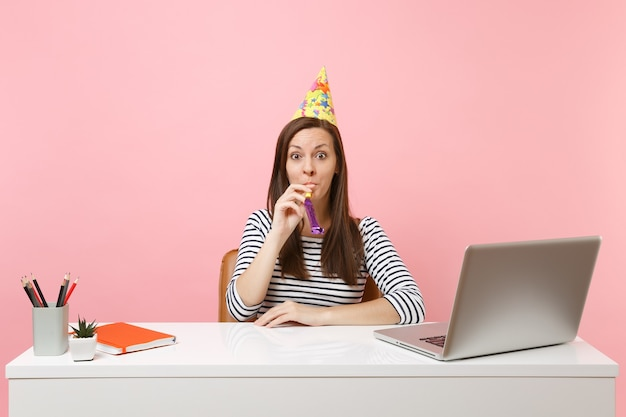 Young shocked woman in birthday party hat with playing pipe celebrating while sit work at white desk with pc laptop
