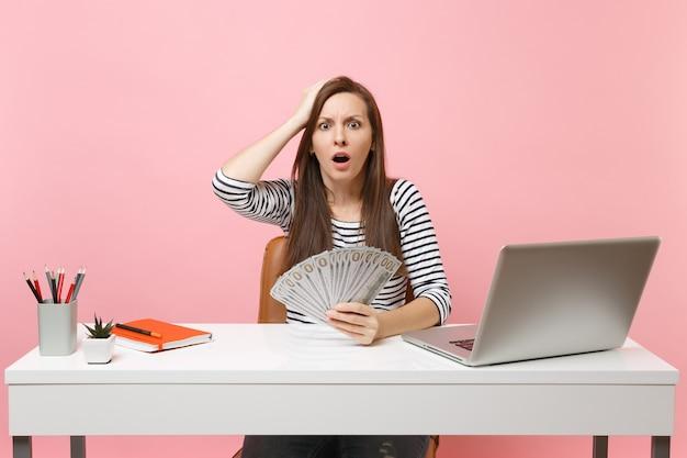 Giovane donna scioccata aggrappata alla testa tenendo in mano un sacco di dollari in denaro contante lavora in ufficio alla scrivania bianca con un computer portatile