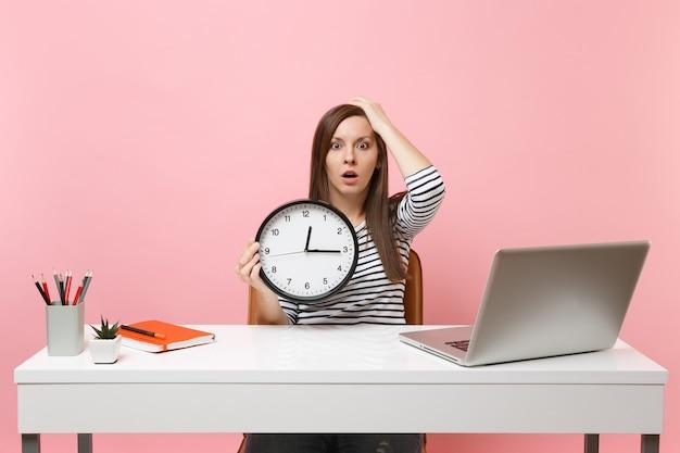 Молодая потрясенная женщина, цепляющаяся за голову, держит будильник, пока сидит работает в офисе с ноутбуком, изолированным на пастельно-розовом фоне. достижение бизнес-концепции карьеры. скопируйте пространство. время уходит.