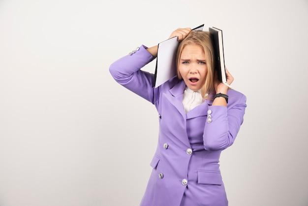 白でタブレットを保持している若いショックを受けた女性。