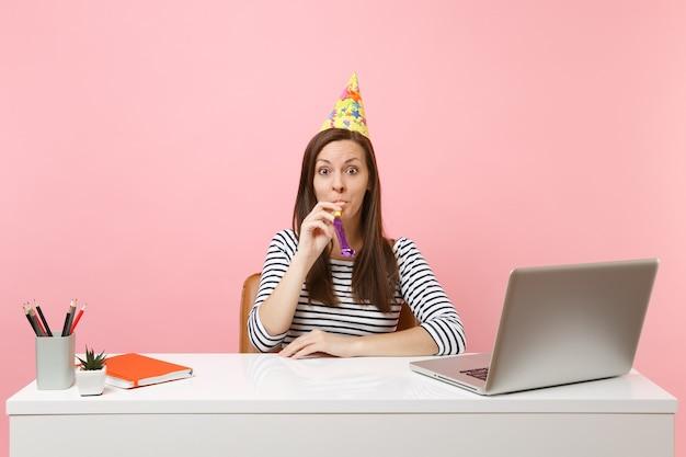 Молодая шокированная женщина в шляпе для вечеринки по случаю дня рождения с игральной трубкой празднует, сидя за белым столом с ноутбуком