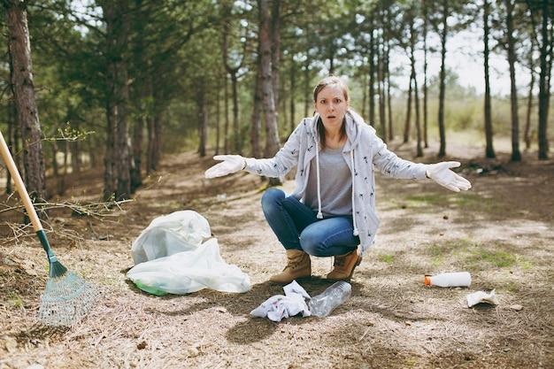 평상복을 입고 장갑을 끼고 쓰레기를 청소하고 공원의 쓰레기 봉투 근처에 손을 뻗은 젊은 충격을 받은 여성. 환경오염 문제