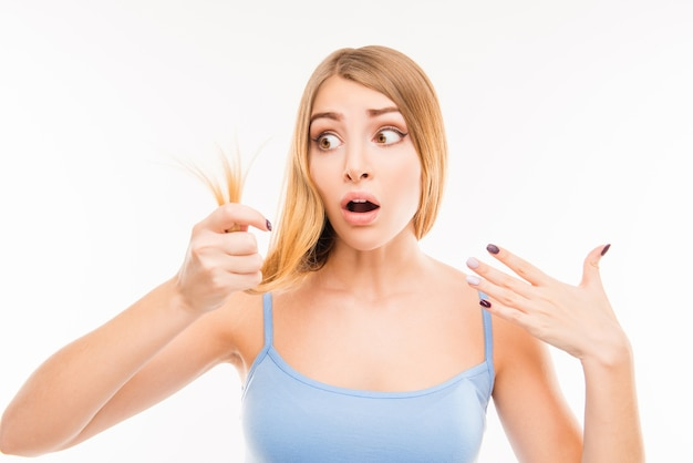 Young shocked woman looking at damaged split ends