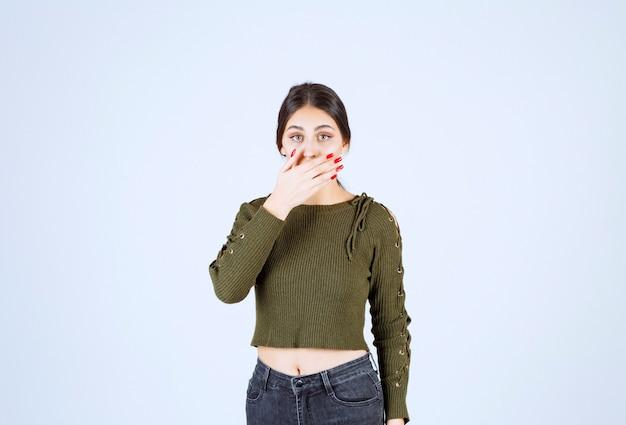 Молодая шокированная модель женщины прикрывает рот рукой.