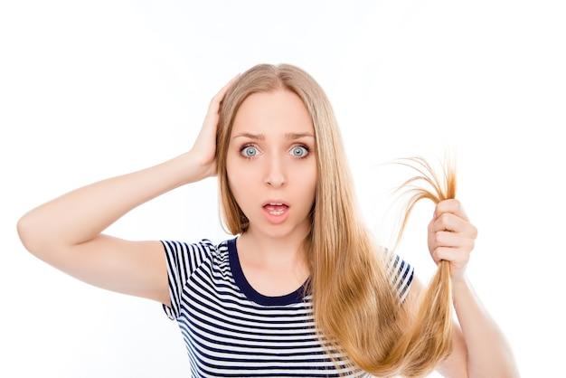Молодая шокированная женщина показывает свои поврежденные секущиеся кончики волос