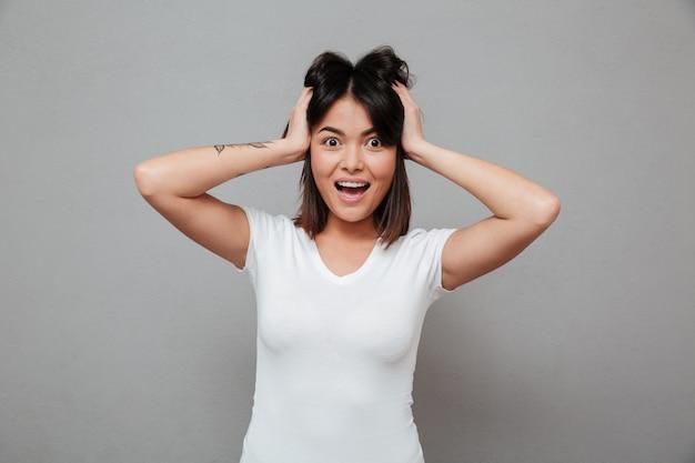 灰色の壁の上に立っている若いショックを受けた女性。