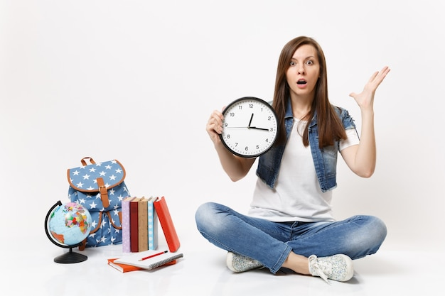 Young shocked woman student in denim clothes holding alarm clock spreading hands sitting near globe, backpack, school books isolated
