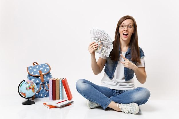 Giovane studentessa scioccata che punta il dito indice su un sacco di dollari, denaro contante seduto vicino allo zaino del globo, libri scolastici isolati