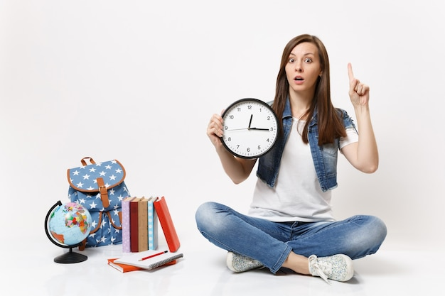 Young shocked woman student pointing index finger up holding alarm clock sitting near globe, backpack, school books isolated