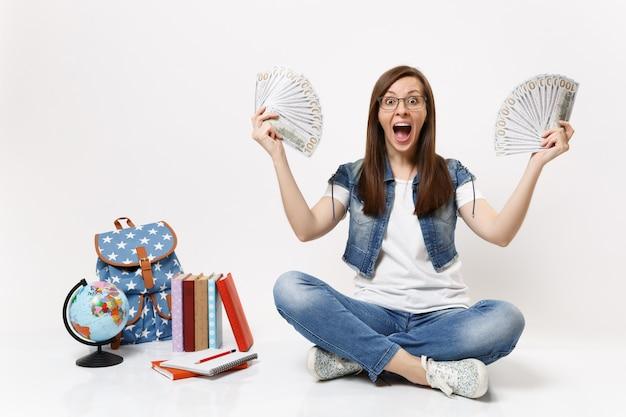 Молодая потрясенная студентка кричит, раздвигая руки, держа пачку долларов, наличные деньги сидят рядом с земным шаром, рюкзаком, изолированными книгами