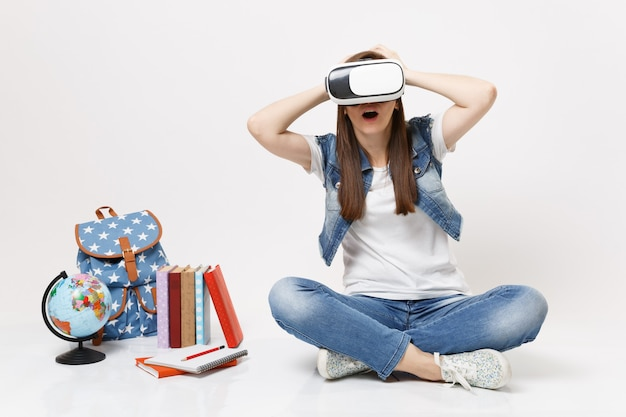 Young shocked woman student wearing virtual reality glasses clinging to head enjoying sitting near globe, backpack, school books isolated