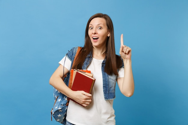 Young shocked woman student with backpack pointing index finger up on copy space and got new idea holding school books isolated on blue background. education in high school university college concept.