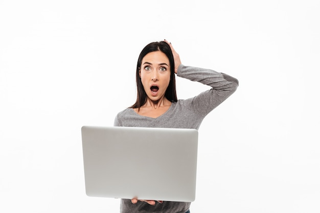Young shocked woman using laptop computer.