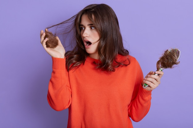 Young shocked woman wearing casual outfit posing isolated over lilac wall, having problem with hair, suffering from hair loss, holding lock of hair in hands and keeps mouth opened.