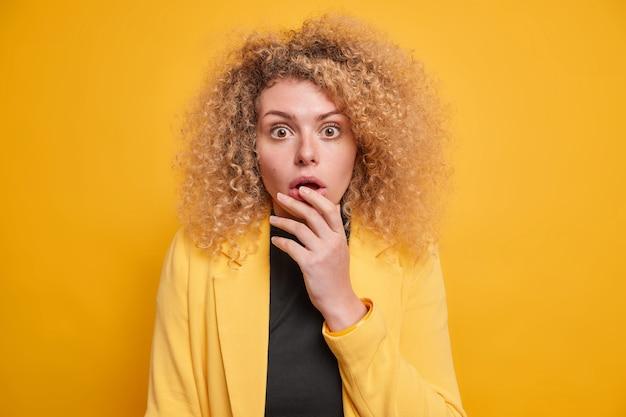 Молодая потрясенная женщина с вьющимися волосами стоит безмолвно вздыхает от удивления, не может поверить в ужасные новости, выражает великое чудо в элегантной куртке, изолированной на ярко-желтом заднем фоне. реакция