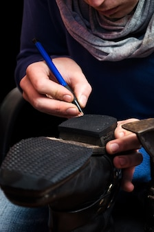 Young shoemaker making a new drafts for new pair of shoes heel - shoes making process