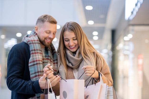 ショッピングモールで季節のセールで購入したものを見て、紙袋を持った若い買い物中毒者
