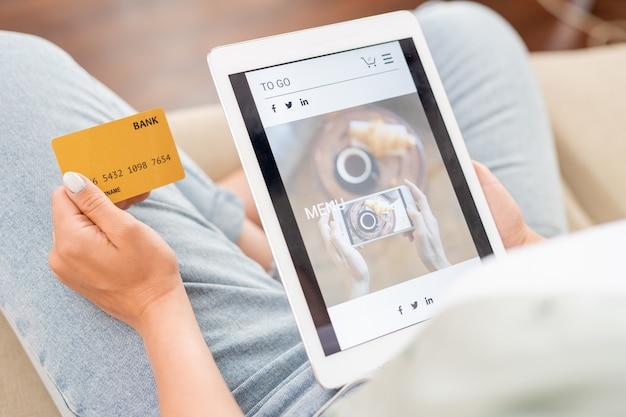 オンラインショップで商品をスクロールしながらクレジットカードとタッチパッドを持っている若い買い物客