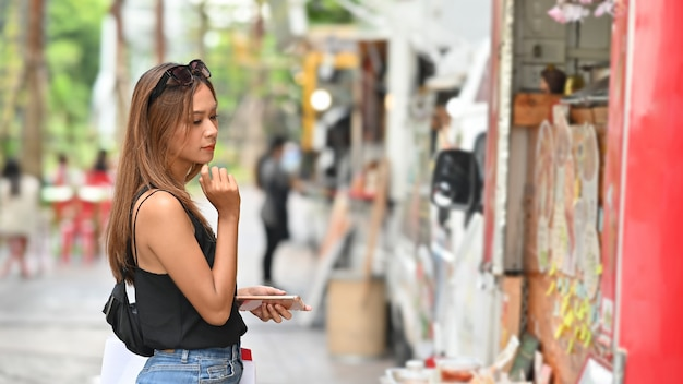Young shopping woman waiting and looking on food truck in park, food street concept.