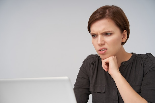 Young short haired brunette woman with natural makeup leaning her chin with raised hand and frowning eyebrows while looking with displeased face on her laptop