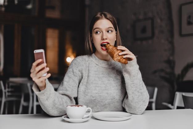 회색 셔츠를 입은 젊은 단발 소녀가 밝은 카페에서 선명한 크로와상을 물고 셀카를 찍습니다.