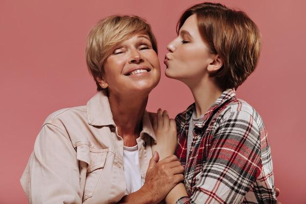 Молодая девушка с короткими волосами в клетчатой красной рубашке целует в щеку свою бабушку со светлыми волосами в бежевой куртке на розовом фоне.