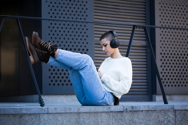 Young short-haired woman sitting and listening to music outdoors