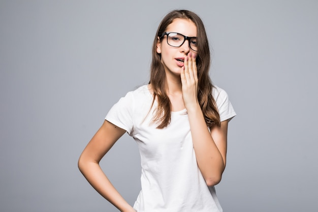 白いtシャツとブルージーンズのメガネで内気な若いきれいな女性は、白いスタジオの背景の前に滞在します。