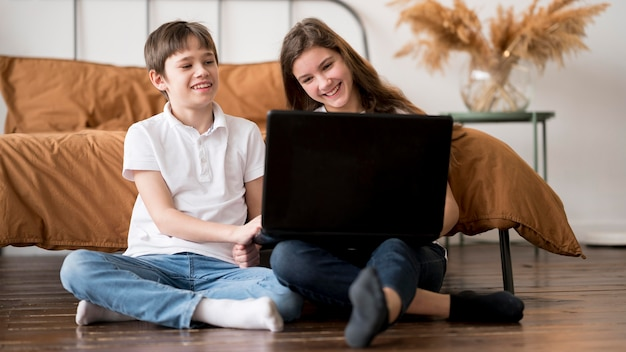 Young sibling using laptop