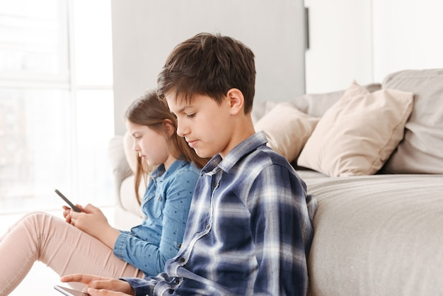 Young siblings girl and boy sitting on floor near sofa at home, and both using smartphone