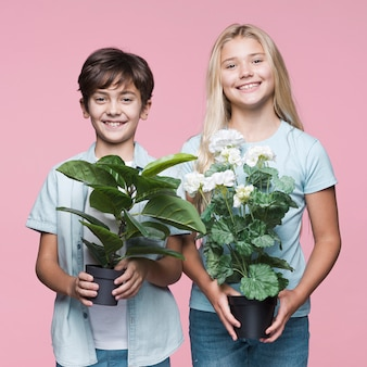 Young siblings holding flowers pot