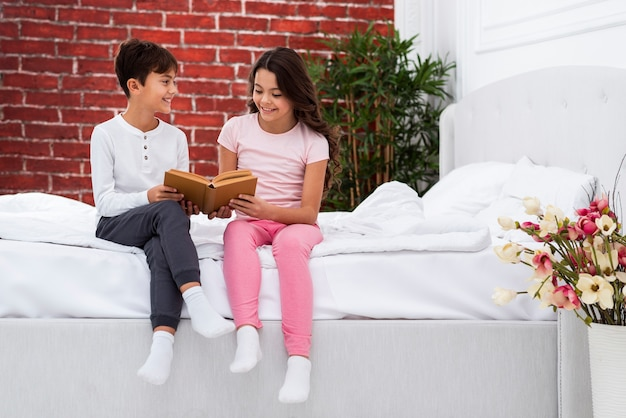 Young siblings at home on bed riding