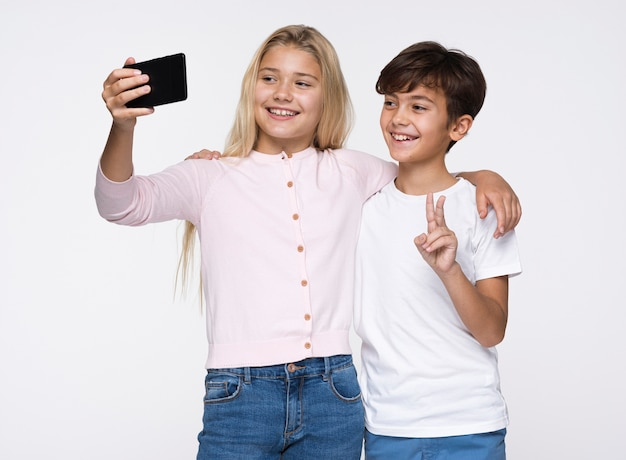 Young siblings taking selfies