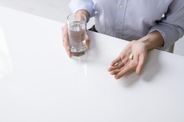 Молодая больная женщина или бизнесвумен в рубашке, держа стакан воды и таблетку, сидя за столом