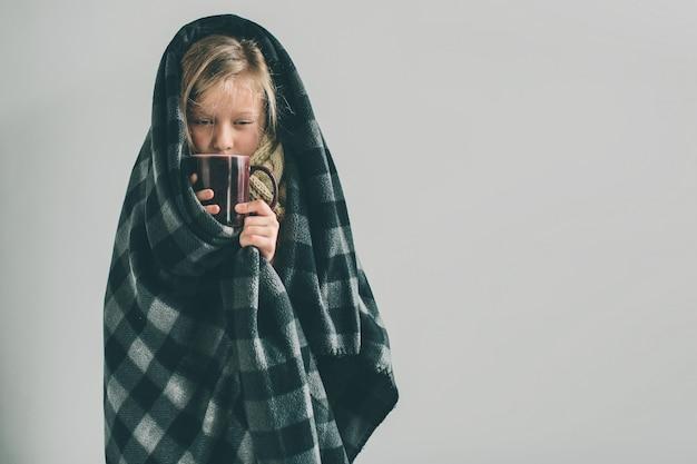 Молодая больная девушка с одеялом и горячим напитком