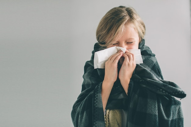 Young sick girl with handkerchier and blanket