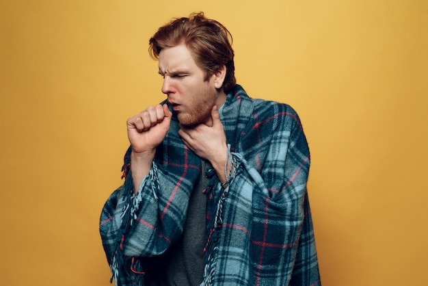 Young sick guy wrapped in plaid coughing