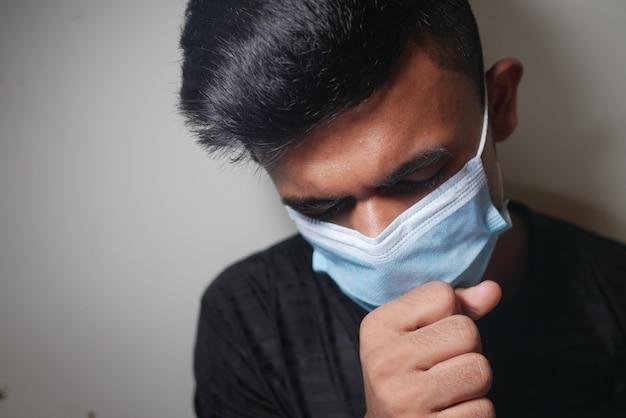 若い病人が咳をして白い壁にくしゃみをする