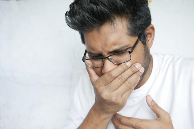 Молодой больной человек кашляет и чихает