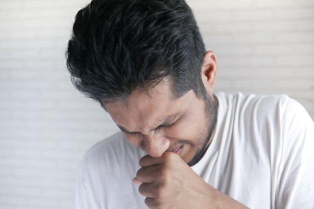 기침과 재채기를 하는 젊은 아픈 남자
