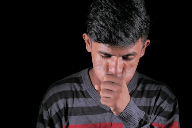 Молодой больной кашель изолирован на черном